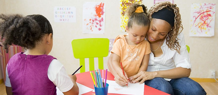 Early Childhood Educator helping children color pictures.