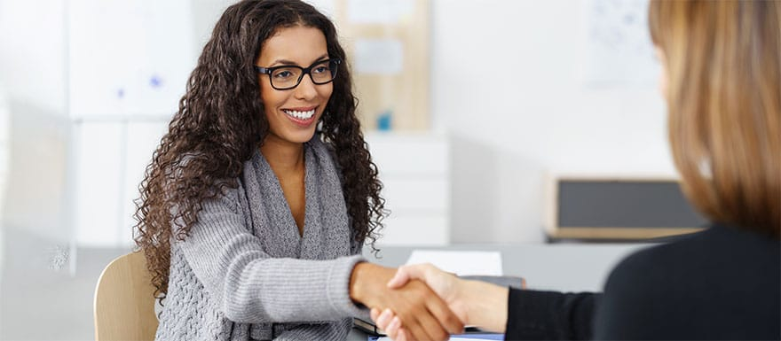 Female student shaking hands with a Financial Aid Advisor.