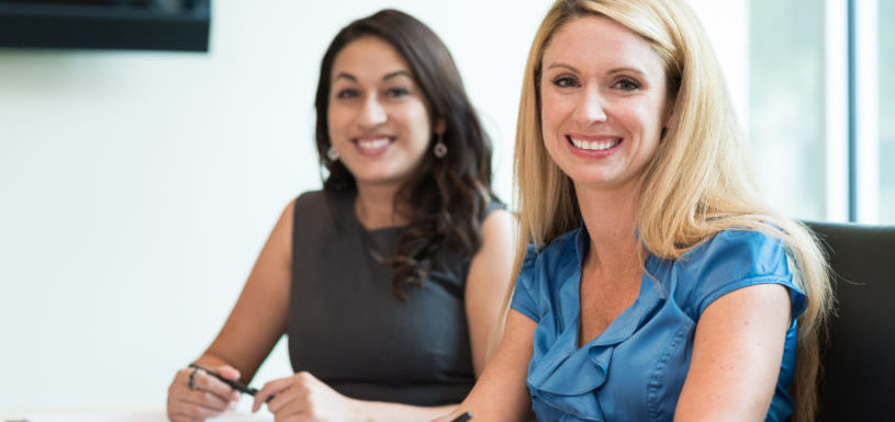 Two women in business casual sit at a desk and smile.
