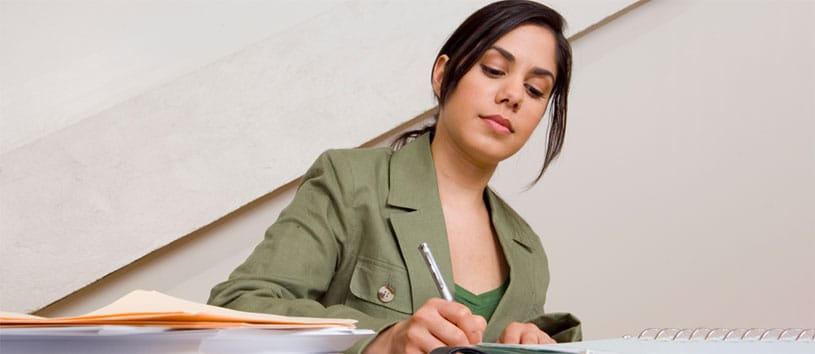 An Accounting and Human Resources professional makes notes in a notepad at a desk.