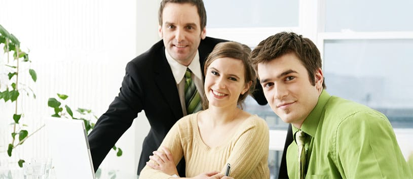 Three business professionals sit at a desk and use a computer.