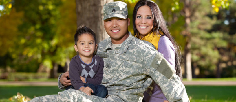A military veteran sits outside with his wife and son