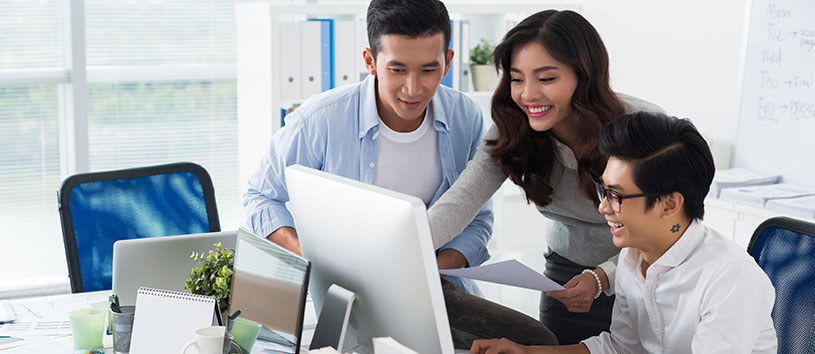 International students looking at a computer.