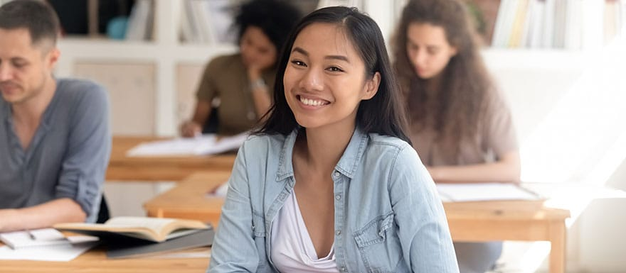 International student smiling in a classroom.